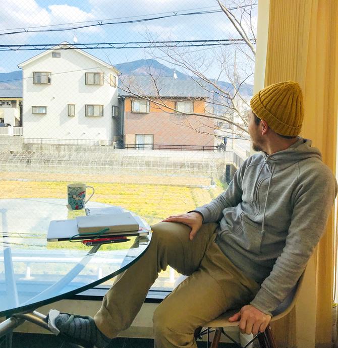 遠くに見える比叡山の頂を眺める男